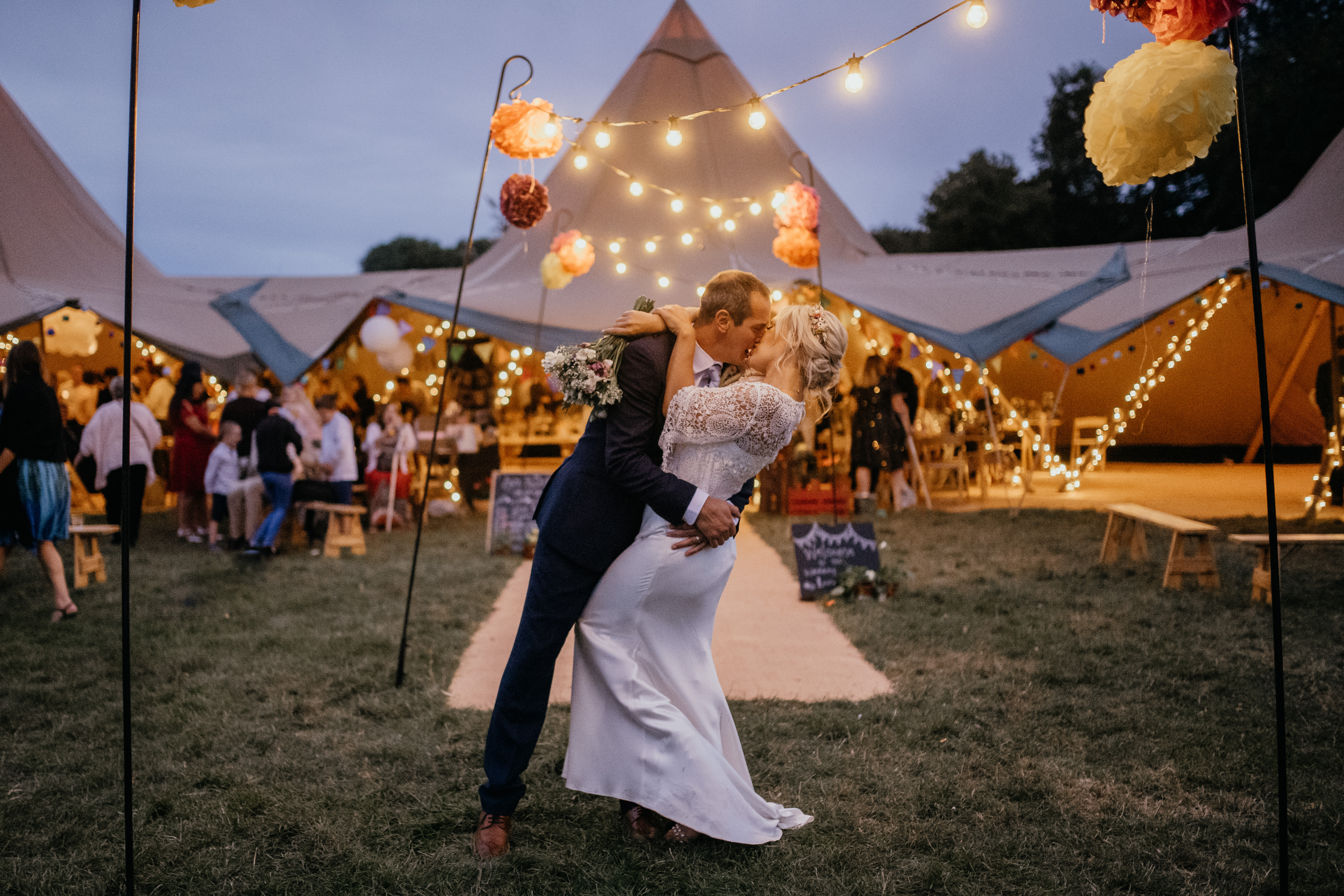 groom kisses bride with fairy lights
