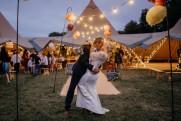 groom kisses bride with fairy lights